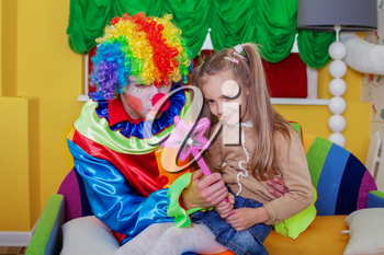 Little girl playing with cheerful clown in funny costume. Friendship concept