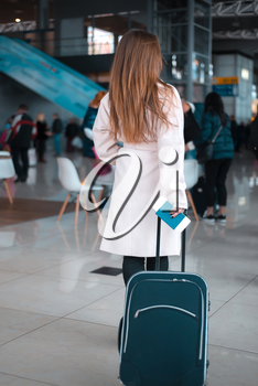Young female traveller walking the airport hall draging suitcase. Blured airport cafe on the background