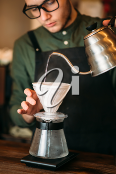 Waiter in black apron and eyeglasses pours hot boiled water in a coffee pot standing on bar counter.