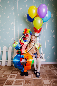 Happy little girl with the clown shake on a swing. Clown hold air balloons in his hands.