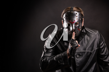 Serial maniac in hockey mask and cutted leather gloves show do not talk sign leaning his index finger to his lips. Black background