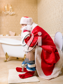 Santa Claus with his pants down sitting on the toilet. Christmas humor