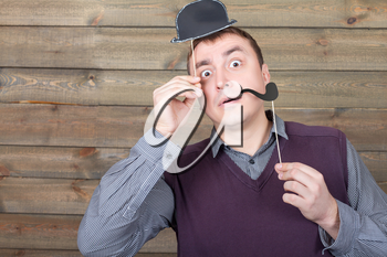 Young male with funny hat and smoking pipe on a sticks in hand, wooden background. Fun photo props and accessories for shoots
