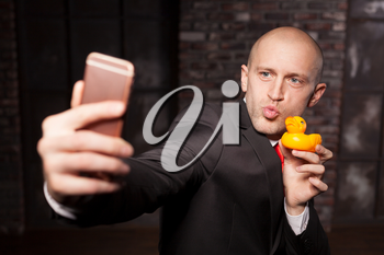 Special agent makes selfie with little toy duck on phone camera. Contract killer in suit and red tie shows his fears and secrets. Hired murderer wallpaper or background concept