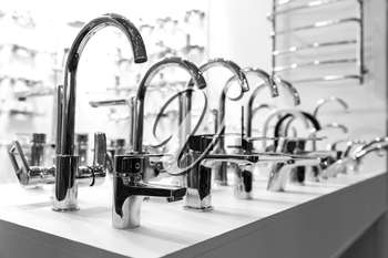 Rows of new chrome faucets in plumbing shop, closeup, nobody. Sanitary equipment