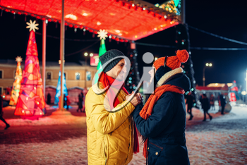 Evening winter walk, love couple on the square. Man and woman having romantic meeting on city street with lights