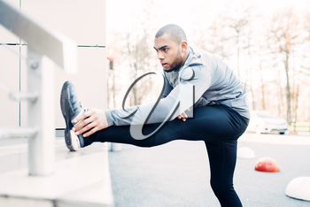 Male athlete doing stretching exercise before run. Jogger on morning fitness workout. Runner in sportswear on training outdoor