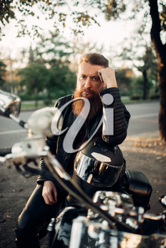 Biker sitting on a motorcycle leaning on a helmet. Vintage bike, rider and his two-wheeled friend, freedom lifestyle, biking