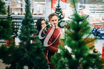 Couple buying christmas tree in supermarket. December shopping, choosing of holiday decorations