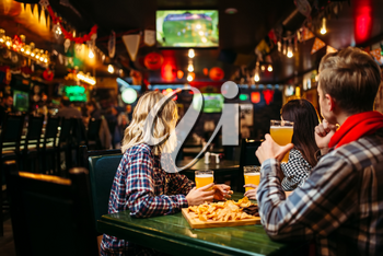 Football fans watching match and drinks beer at the table in sports bar. Tv broadcasting, young friends leisures in pub