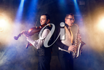 Male saxophonist and violinist playing classical music on sax and violin. Jazz band on the stage in action