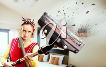 Angry housewife in apron with vacuum cleaner, flying pieces of dirt, bedroom interior on background. Crazy female person performs general cleaning, ruthless fight against dust