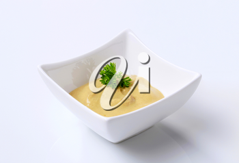 Creamy mustard in a small square bowl