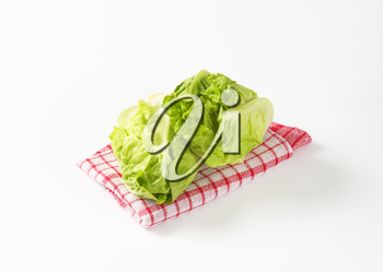 Fresh little gem lettuce heads on checked dish towel
