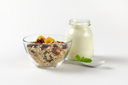 bowl of oat flakes with raisins and jar of white yogurt on off-white background