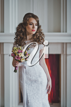 The girl with a bunch of flowers in a wedding dress costs at a fireplace.