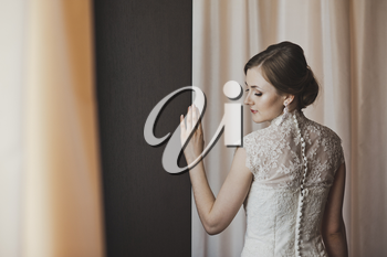 Girl in a wedding dress stands near the curtains.