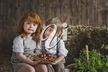 A girl and a boy holding a dish with Easter eggs.