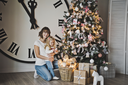 Mother and her daughter on background of great white watches and Christmas trees.