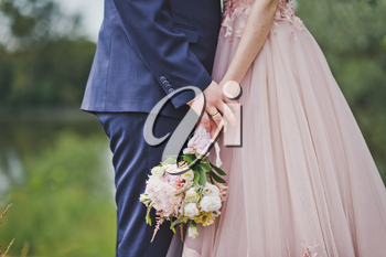 Bride and groom holding a bouquet of flowers.