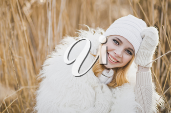 Close-up portrait of girl in white furry jacket and hat in the winter among the reeds.