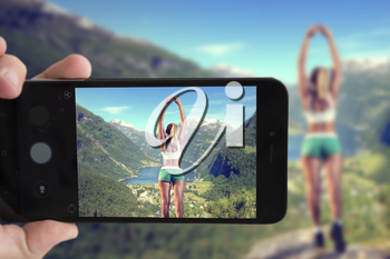 blogger takes a smartphone girl on the edge of the mountain