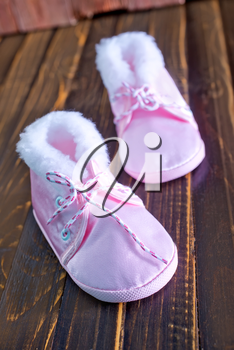 baby shoes on the wooden table, pink shoes