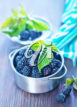 fresh blackberry in metal bowl and on a table