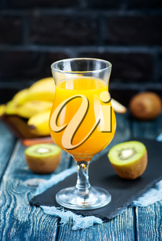 juice from kiwi and banana in the glass and on a table