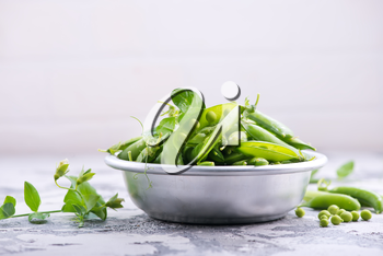 green peas in bowl and on a table