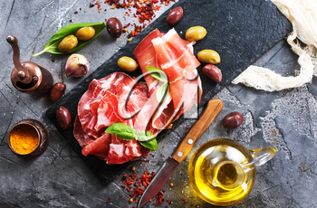 prosciutto with olives and spice on a table