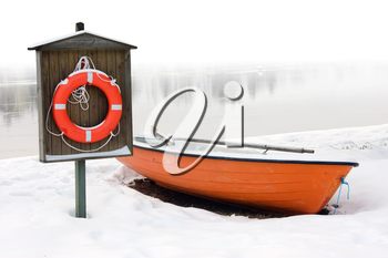 safety and lifesaving concept: orange lifeboat and orange lifebuoy on a snow-covered riverside in winter