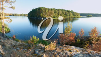 Ladoga lake with island under summer sunset light panoramic view