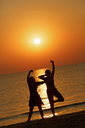 Two girls dancing on the background of the dawn. Shallow depth of field.