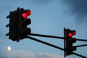 Traffic light with red light against the evening sky. Shallow depth of field. Selective focus.