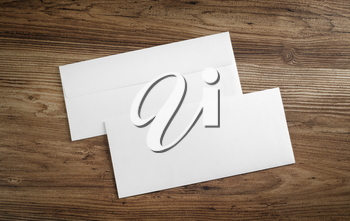 Blank paper envelopes on wooden table background. Front and back side. Template for your design. Top view.