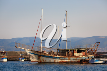 Nesebar, Bulgaria - September 10, 2014: Old rusty ship and boats at the pier in the old town of Nessebar, Bulgaria.