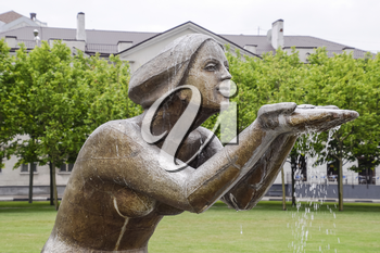 Statue of kneeling woman in the fountain. Water flowing from the hands of the statue.
