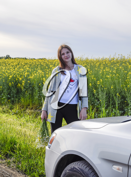 A beautiful young woman with a bouquet of daisies stands near a silver car.