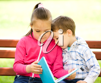Little boy and girl is reading book while sitting on green grass outdoors
