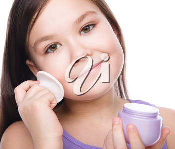 Beautiful girl applying moisturizer cosmetic cream on face, isolated over white