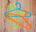 Set of colorful plastic clothes hangers on wooden background