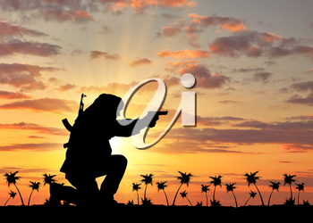Concept of terrorism. Silhouette of a terrorist with a rifle on a background of sunset and palm trees