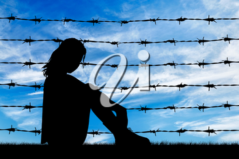 Concept of refugee. Silhouette Despair refugee woman near the fence of barbed wire