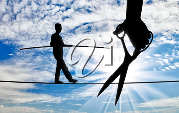 Silhouette of a businessman walking on a tightrope balances and a hand with scissors intends to cut the rope. Concept of danger and risks in business