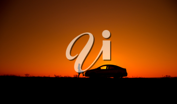 Young girl with and broken car. Silhouette of sedan car with girl on the background of beautiful sunset