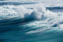 Frozen motion of large wave or breaker approaching shore and short shutter speed freezing the water into droplets
