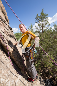 Senior male climber well equipped with cams and caribiners on Turtle Rocks near Buena Vista Colorado