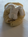 Unusual animal shaped like a dog or teddy bear created from rolled and folded towels on top of bed sheets in hotel