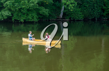 Male and female caucasian couple paddling a yellow canoe on a very calm morning on tree lined lake
